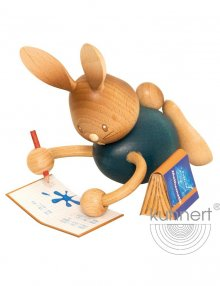 Easter bunny Stupsi in homeschooling, lying with exercise book