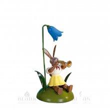 Blank Osterhase sitzend mit Glockenblume und Trompete